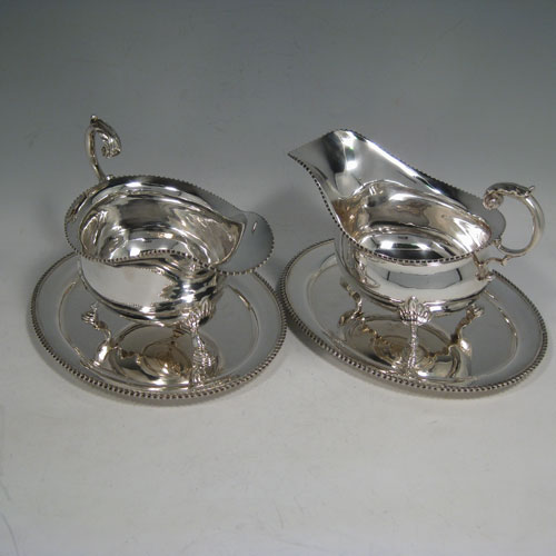 Sterling silver pair of sauce boats on stands, having gadroon edges, scroll handles, and sitting on three shell and hoof feet. Made in Birmingham in 1978. Length of sauce boats 18 cms (7 inches), height 12 cms (4.75 inches), width 10 cms (4 inches). Total weight approx. 909g (29.3 troy ounces).