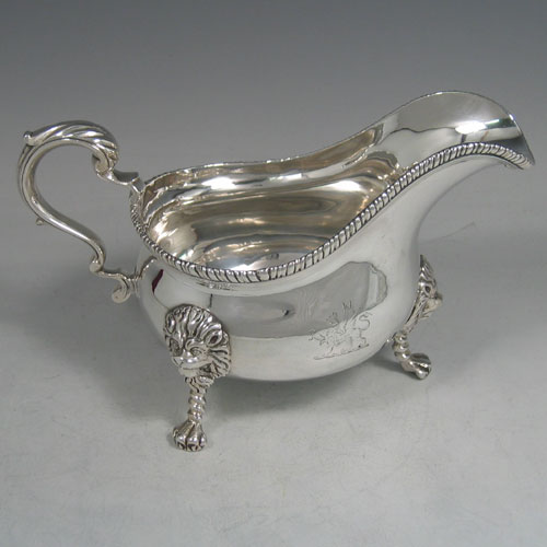An Antique Victorian sterling silver single large sauce boat, having a plain baluster body, with an applied gadroon border, a cast scroll handle, and sitting on three cast lion-mask feet. Made by Frederick Brasted of London in 1870. The dimensions of this fine hand-made silver sauce boat are length 19.5 cms (7.75 inches), height 11.4 cms (4.5 inches), width 10 cms (4 inches), and it weighs approx. 384g (12.4 troy ounces). Please note that this item is crested.