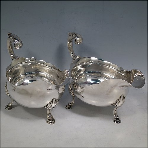 An Antique Georgian Sterling Silver pair of large George III sauce or gravy boats, having plain bellied bodies, with Chippendale borders, cast scroll handles, and sitting on three cast hoof feet with shell shoulders. Made by John Deacon (Possibly) of London in 1773/74. The dimensions of these fine hand-made antique silver sauce boats are length 18 cms (7 inches), width 10 cms (4 inches), height 13 cms (5 inches), and they weigh a total of 568g (18 troy ounces).