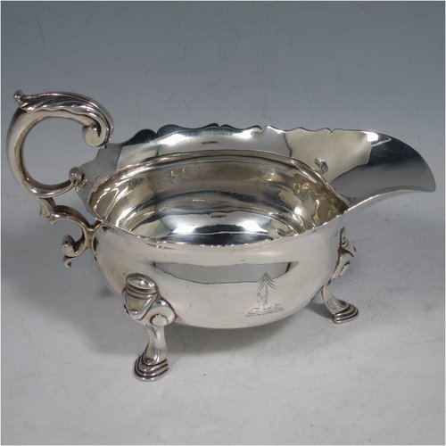 An Antique Georgian Sterling Silver George II sauce or gravy boat, having a plain baluster body, with a Chippendale border, cast scroll handle, and sitting on three cast hoof feet with scroll shoulders. Made in London in 1746. The dimensions of this fine hand-made antique silver sauce boat are length 16.5 cms (6.5 inches), width 10 cms (4 inches), height 10 cms (4 inches), and it weighs 280g (9 troy ounces). Please note that this item is crested.