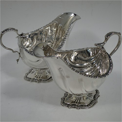 A very handsome Antique Edwardian Sterling Silver pair of sauce boats or gravy boats in a Georgian George II style, having bellied bodies with hand-chased swirl fluting, with applied gadroon borders, cast scroll handles with anthemion leaf tops, and sitting on shaped oval pedestal feet. Made by D & J Welby of London in 1904. The dimensions of these fine hand-made antique silver gravy or sauce boats are length 16.5 cms (6.5 inches), width 10 cms (4 inches), height 11.5 cms (4.5 inches), and they weigh a total of approx. 480g (15.5 troy ounces).