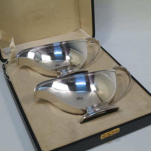 A stylish pair of Sterling Silver Art Deco sauce boats, having plain half-moon style bodies, scroll side-handles with thumb-pieces, square cross-section spouts, and sitting on a rectangular pedestal feet, all in their original cream satin and velvet-lined presentation box. Made by the Adie Brothers of Birmingham in 1937. The dimensions of this fine hand-made pair of silver sauce boats are length 16.5 cms (6.5 inches), height 7.5 cms (3 inches), width 7 cms (2.75 inches), and with a total weight of approx. 312g (10 troy ounces). Please note that the lids satin retaining strap is broken.