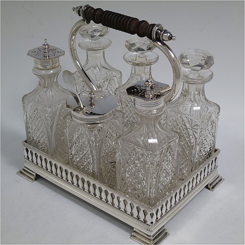 A very pretty Antique Victorian Silver Plated and hand-cut crystal cruet set, having six crystal bottles with original stoppers and silver mounts, sitting in a rectangular hand-pierced gallery frame with reeded borders, on four cast stepped feet. Made by Henry Hobson and Son, of Sheffield in ca. 1890. The dimensions of this fine hand-made antique silver-plated cruet set are height of frame 19 cms (7.5 inches), length 18.5 cms (7.3 inches), and width 14 cms (5.5 inches).
