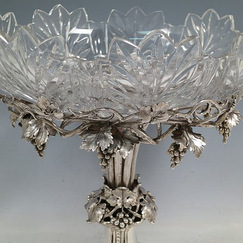 A very pretty Antique Victorian Sterling Silver compote or dessert stand with applied cast grape vine work, and sitting on a pedestal foot with hand-chased anthemion leaves, together with a hand-cut crystal bowl. Made by the Barnard Brothers of London in 1856. The dimensions of this fine hand-made antique silver and crystal dessert or compote stand are height 28 cms (11 inches), diameter of bowl 25.5 cms (10 inches), and it weighs approx. 1,273g (41 troy ounces).