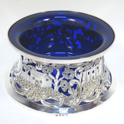 A very beautiful Irish Antique Edwardian Sterling Silver large table dish ring, having a hand-pierced and chased body decorated with scrolls, two cottages, a castle, and a bridge, a vacant oval cartouche, and a blue-glass liner. Made by Edmund Johnson of Dublin in 1910. The dimensions of this fine hand-made antique silver dish ring are height 9 cms (3.5 inches), diameter at base 19 cms (7.5 inches), and it weighs approx. 302g (9.7 troy ounces).