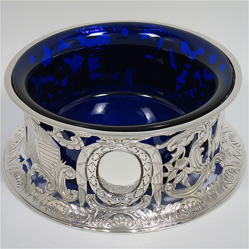 An Antique Victorian Sterling Silver large table dish ring in an Irish style, having a hand-pierced and chased body decorated with pastoral scenes, figures, animals, a vacant oval cartouche, and a blue-glass liner. Made by D. and J. Welby of London in 1894. The dimensions of this fine hand-made antique silver dish ring are height 7.5 cms (3 inches), diameter at base 19 cms (7.5 inches), and it weighs approx. 351g (11.3 troy ounces).