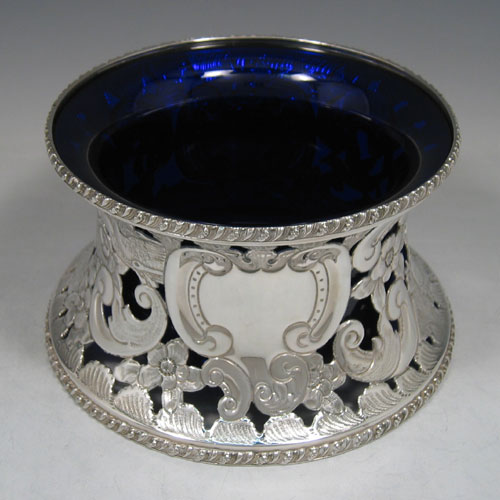 Antique Georgian Old Sheffield plated dish ring, having a hand-pierced and chased body with floral decoration and figural work, appled gadroon borders, and a blue-glass liner. Made circa 1780. Height 11 cms (4.5 inches), diameter 18 cms (7 inches).