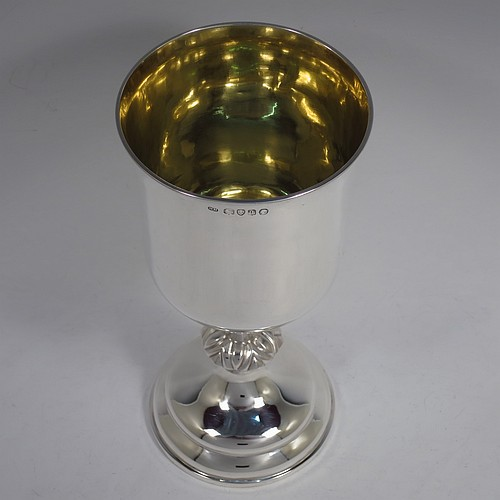 A large and handsome Antique Victorian Sterling Silver altar chalice, having a round straight-sided body with tucked under belly, an applied reeded top border, a gold-gilt interior, a middle baluster with fluted cabochon decoration, and a spreading round stepped pedestal foot. Made by Henry Holland of London in 1871. The dimensions of this fine hand-made antique silver chalice are height 23.5 cms (9.25 inches), diameter at lip 11 cms (4.25 inches), and it weighs approx. 382g (12.3 troy ounces). Please note that this has a classically engraved Christogram within sunburst on main body.