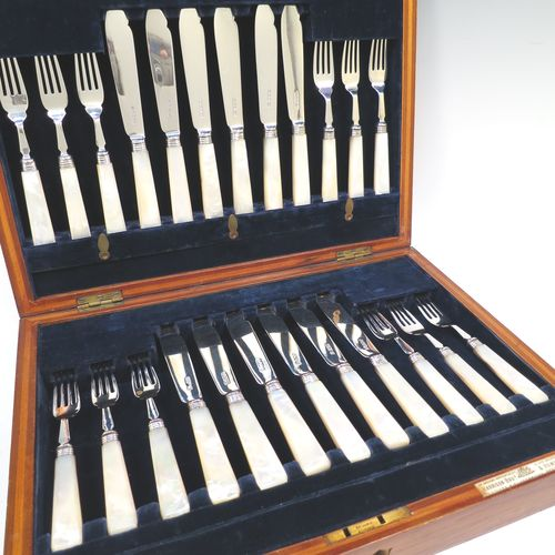 A very pretty Antique Sterling Silver and mother of pearl handled fish set for twelve people, having plain blades and tines, and with hand-cut mother-of-pearl handles, all fitted into their original dark blue velvet-lined oak presentation box. All made by John Sanderson of Sheffield in 1912. The dimensions of these fine hand-made antique silver and mother of pearl fish-eaters are length of knife 19 cms (7.5 inches), and fork 16 cms (6.3 inches).