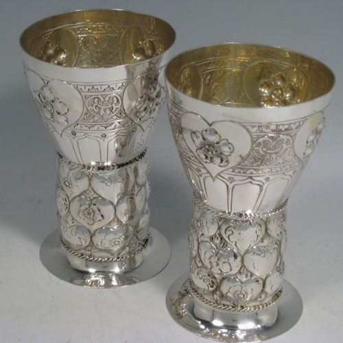 Antique Victorian sterling silver pair of Arts and Crafts goblets, having hand-chased round tapering bodies with floral and heart-shaped work, a gold-gilt interior, and sitting on a round pedestal foot having hand-chased hearts separated by applied rope-twist bands. Imported into Chester in 1899. Height 12 cms (4.75 inches), diameter at top 7.5 cms (3 inches). Total weight approx. 289g (9.3 troy ounces).