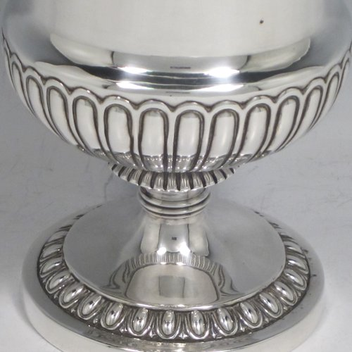 Antique Georgian sterling silver Regency goblet, having a hand-chased campagna style body, with an applied band of grapevine decoration, a half-fluted lower body, and sitting on a pedestal foot. Made in London in 1812. The dimensions of this fine hand-made silver goblet are height 15 cms (6 inches), diameter at lip 10 cms (4 inches), and it weighs approx. 386g (12.5 troy ounces).