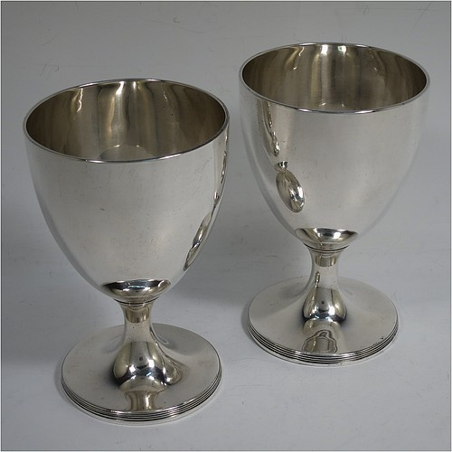 A very handsome pair of Antique Georgian Sterling Silver goblets, having plain round bodies with tapering sides, and sitting on pedestal feet with reeded borders. Made by John Robins of London in 1800. The dimensions of this fine hand-made pair of antique silver goblets are height 12 cms (4.75 inches), diameter at top 8 cms (3 inches), and the total weight is approx. 384g (12.4 troy ounces).