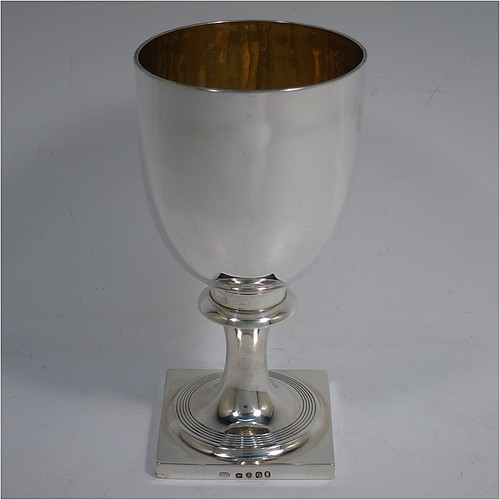A very handsome Antique Georgian Sterling Silver heavy goblet, having a plain round tapering body with a gold-gilt interior, and sitting on a pedestal foot with reeded decoration and a square base. Made by Thomas Hobbs of London in 1811. The dimensions of this fine hand-made antique silver goblet are height 17 cms (6.75 inches), diameter at lip 9 cms (3.5 inches), and it weighs approx. 312g (10 troy ounces).