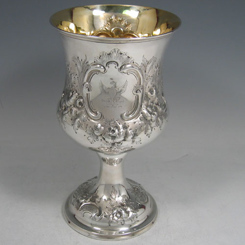 Antique Victorian sterling silver large goblet, having a round baluster body with hand-chased floral decoration, with two cartouches either side (one crested and the other with a military presentation inscription), a gold-gilt interior, and sitting on a pedestal foot. Made by Alexander Macrae of London in 1876. The dimensions of this fine hand-made silver goblet are height 20 cms (8 inches), diameter at lip 11.5 cms (4.5 inches), and it weighs approx. 309g (10 troy ounces).