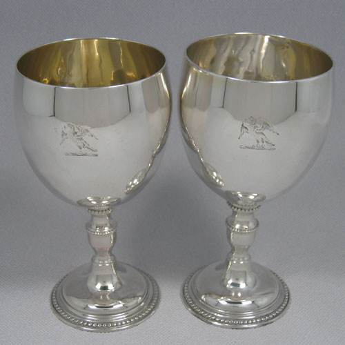 Antique Georgian sterling silver pair of goblets made in London in 1774. With bead edges on base of foot, and having a crest on main body. Height 17 cms, diameter 9 cms. Weight approx. 17 troy ounces.