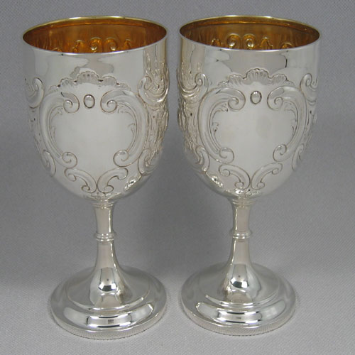 Sterling silver and gold-gilt pair of florally hand-chased goblets made by Samuel Watton Smith of London in 1914. Height 19 cms, diameter 8.5 cms. Weight approx. 18 troy ounces.