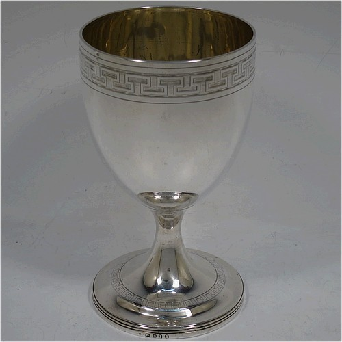 A large and very handsome Antique Georgian Sterling Silver goblet, having a round tapering body with a top band of hand-engraved Greek-key decoration, sitting on a pedestal foot with a reeded border, and with a gold-gilt interior. Made in London in 1804. The dimensions of this fine hand-made antique silver goblet are height 16.5 cms (6.5 inches), diameter at lip 9 cms (3.5 inches), and it weighs approx. 278g (9 troy ounces).