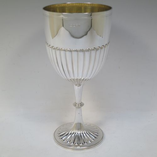 A very pretty and large Antique Edwardian Sterling Silver goblet, having a round tapering body with hand-chased half-fluted decoration, sitting on a pedestal foot with matching decoration and a bead-edged border, and with a gold-gilt interior. Made by Henry Atkins of Sheffield in 1902. The dimensions of this fine hand-made antique silver goblet are height 23.5 cms (9.25 inches), diameter at lip 11 cms (4.25 inches), and it weighs approx. 310g (10 troy ounces).