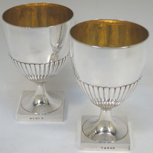A very fine and handsome Antique Georgian Sterling Silver pair of goblets, having round bodies with hand-chased half-fluted decoration, gold-gilt interiors, and sitting on pedestal feet with square bases. Made by John Wakelin and Robert Garrard of London in 1796. The dimensions of this fine hand-made pair of antique silver goblets are height 15 cms (6 inches), diameter at top 9.5 cms (3.75 inches), and their total weight is approx. 509g (16.5 troy ounces).