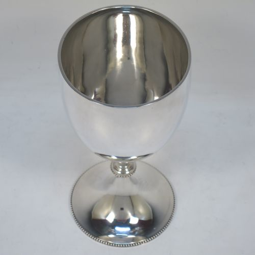 A pretty Antique Victorian Sterling Silver goblet, having a plain round tapering body, and sitting on a pedestal foot with an applied bead-edged border. Made by Edward Hutton of London in 1881. The dimensions of this fine hand-made antique silver goblet are height 16 cms (6.3 inches), diameter at lip 8.5 cms (3.3 inches), and it weighs approx. 212g (6.8 troy ounces).