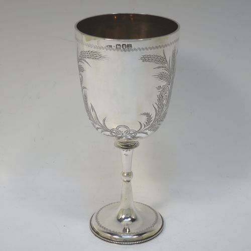A very pretty Antique Victorian Sterling Silver goblet, having a round straight-sided and bellied body with hand-engraved floral and wheat-sheaf decoration, with a vacant cartouche on one side, a gold-gilt interior, and sitting on a pedestal foot with hand-engraved decoration and an applied bead-edged border. Made by George Maudsley Jackson of London in 1892. The dimensions of this fine hand-made antique silver goblet are height 18.5 cms (7.3 inches), diameter at lip 8.5 cms (3.3 inches), and it weighs approx. 175g (5.6 troy ounces).