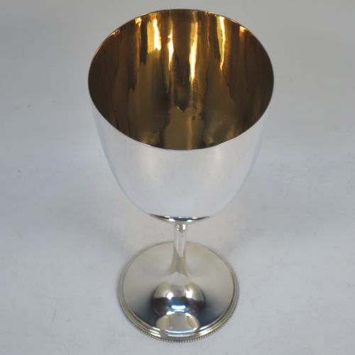 A handsome Antique Edwardian Sterling Silver goblet, having a plain round tapering body with a gold-gilt interior, and sitting on a plain pedestal foot with an applied bead border. Made by Henry Wilkinson of Sheffield in 1905. The dimensions of this fine hand-made antique silver goblet are height 16.5 cms (6.5 inches), diameter at lip 8 cms (3.25 inches), and it weighs approx. 124g (4 troy ounces).