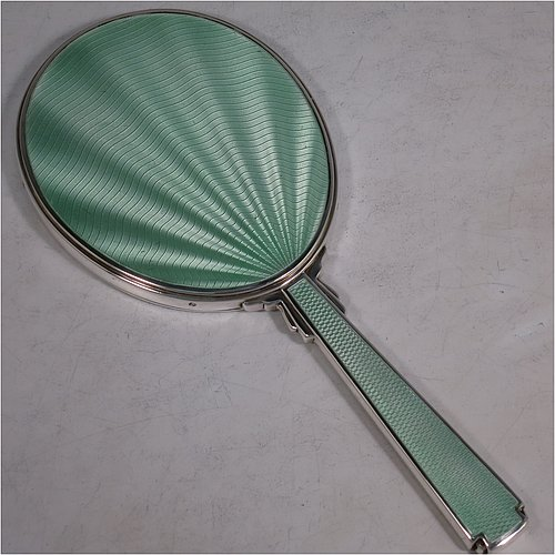 A Sterling Silver Art Deco style hand-mirror, having an oval body and a square cross-section handle, with green enamelled sun-burst style decoration, and an original bevelled mirror. Made by Robert Comyns of London in 1945. The dimensions of this fine hand-made Art Deco silver and green enamelled hand mirror are length 25.5 cms (10 inches), and width 11 cms (4.3 inches).