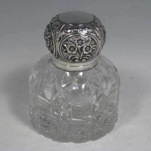 Antique Victorian Art Nouveau sterling silver inkstand, having a hand-chased hinged lid with floral decoration, a glass insert for a smaller amount of ink, and a heavy hand-cut round crystal body that can hold a large amount of ink, with a star cut base. Made by Mappin and Webb of London in 1899. Height 12.5 cms (5 inches), diameter 10 cms (4 inches).