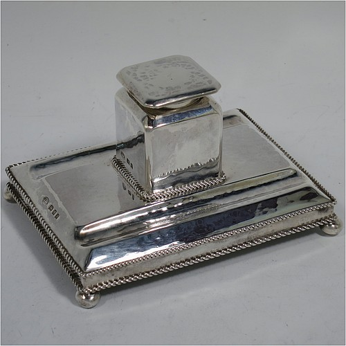 A very pretty Sterling Silver inkstand, in an Arts and Crafts hand-hammered or plenished style, having a single inkwell with a hinged lid and removable glass liner, sitting on a stand with two pen-wells, applied rope-twist borders, and four ball cushion feet. Made in London in 1930. The dimensions of this fine hand-made silver inkstand are height 6.5 cms (2.5 inches), length 11 cms (4.25 inches), width 8 cms (3.25 inches), and it weighs approx. 150g (4.8 troy ounces).