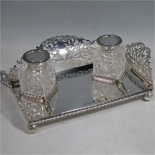 A very pretty Antique Edwardian Sterling Silver galleried double inkstand, having a rectangular body with three hand-pierced scroll-work gallery sides, an applied gadroon front border, two square hand-cut crystal removable ink bottles with round hinged lids, together with two applied pen-rest scrolls, all sitting on four ball feet. Made by George Wish of Sheffield in 1905. The dimensions of this fine hand-made antique silver double inkstand are length 22 cms (8.75 inches), width 14 cms (5.5 inches), height 5 cms (2 inches), and it weighs approx. 334g (10.8 troy ounces).