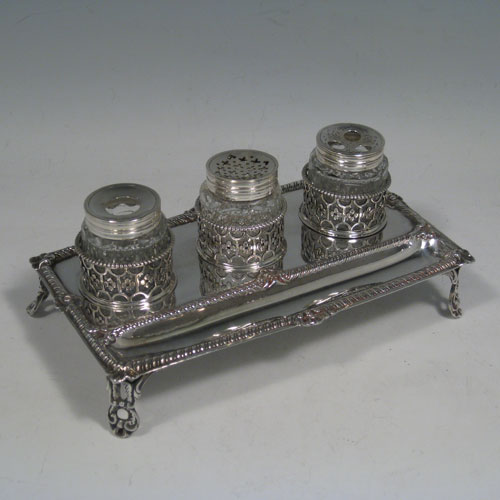 Antique Georgian sterling silver inkstand, having a rectangular body with gadroon and shell border, single pen-well, three hand-cut crystal bottles held within pierced inkwell galleries, all sitting on four cast foliate feet. The glass inkwells are for pens (quills), pounce, and ink. Made by William Plummer of London in 1772. Length 18 cms (7.25 inches), width 11 cms (4.25 inches), height 7.5 cms (3 inches). Weight approx. 240g (7.7 troy ounces).