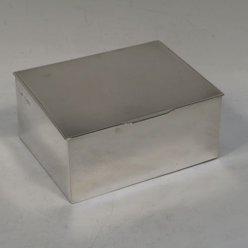 A very stylish Art Deco Sterling Silver jewelery box, having a very plain rectangular shaped body with straight sides, a flat hinged lid with slight engine-turned decoration and thumb-piece, and a dark blue velvet-lined interior, and all sitting on a flat base. Made by Robert Comyns of London in 1934. The dimensions of this fine hand-made silver jewellery box are length 11.5cms (4.5 inches), width 9cms (3.5 inches), and height 5 cms (2 inches)