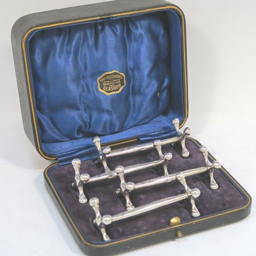 A handsome Sterling Silver set of four knife rests, with traditional cast Jack-style rest ends, and plain round central struts, all in their original dark blue satin and velvet-lined presentation box. Made by Martin Hall and Co., of Sheffield in 1922. The dimensions of this fine hand-made set of four silver knife rests are length 8.5 cms (3.3 inches), height 3 cms (1.25 inches), and they weigh a total of approx. 224g (7.2 troy ounces).