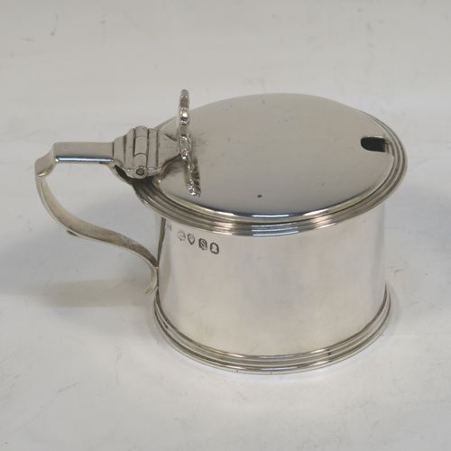 A very elegant Antique Georgian Sterling Silver drum mustard, having a plain cylindrical body, with applied reeded borders, a hinged flat lid with a cast shell thumb-piece, a scroll handle and a blue glass liner. Made by Charles Fox of London in 1833. The dimensions of this fine hand-made antique silver mustard pot are height 6 cms (2.3 inches), diameter 6.5 cms (2.5 inches), and it weighs approx. 90g (3 troy ounces).