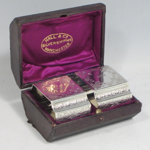 Antique Victorian sterling silver pair of napkin rings, having rectangular bodies with concave corners, and hand-engraved floral decoration, all in their original satin and velvet-lined presentation box. Made in London in 1882. The dimensions of these fine hand-made silver napkin rings are length 5 cms (2 inches), height 3.5 cms (1.3 inch), and they weigh a total of approx. 70g (2.3 troy ounces). Please note that these are crested on one side and numbered on the reverse.