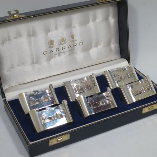A very handsome Sterling Silver set of six napkin rings, having plain bodies with straight sides and hand-cut horse and jockey front panels, all in their original cream satin and dark-blue velvet-lined presentation box. Made by Garrards of Sheffield in 1991. The dimensions of these fine hand-made horse and jockey silver napkin rings are length 5.5 cms (2.25 inches), height 3 cms (1.25 inch), and they weigh a total of approx. 168g (5.4 troy ounces).