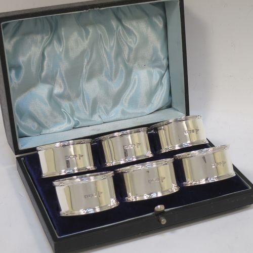 A very handsome Antique Sterling Silver set of six napkin rings, having plain round bodies with straight sides, with applied ribbon and reed borders, all in their original light blue satin and dark-blue velvet-lined presentation box. Made by Walker and Hall of Sheffield in 1915. The dimensions of these fine hand-made antique silver napkin rings are diameter 5 cms (2 inches), height 2.5 cms (1 inch), and they weigh a total of approx. 232g (7.5 troy ounces).