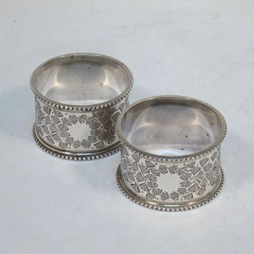 A very pretty pair of Antique Victorian Sterling Silver napkin rings, having round straight-sided bodies with hand-engraved gingko leaf decoration surrounding a vacant cartouche, and bead-edged borders. Made by Martin Hall of Sheffield in 1900. The dimensions of these fine hand-made antique silver napkin rings are diameter 5 cms (2 inches), height 3 cms (1.25 inches), and they weigh a total of approx. 62g (2 troy ounces).
