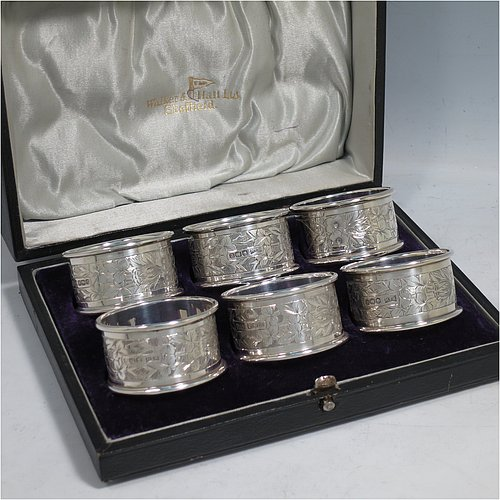 A Sterling Silver set of six napkin rings, having round straight-sided bodies with hand-engraved floral decoration surrounding vacant cartouches, and applied plain borders, all in their original blue satin and velvet-lined presentation box. Made by Walker & Hall of Sheffield in 1922. The dimensions of these fine hand-made silver napkin rings are diameter 4.5 cms (1.75 inches), height 2.5 cms (1 inch), and they weigh a total of approx. 110g (3.5 troy ounces).
