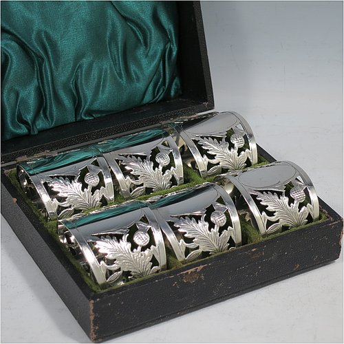 A Sterling Silver set of six napkin rings, having half-circular bodies with flat bases, with hand-pierced and engraved floral Scottish thistle decoration surrounding oval cartouches, all in their original green satin and velvet-lined presentation box. Made by Robert Comyns of Birmingham in 1919. The dimensions of these fine hand-made silver napkin rings are width 5 cms (2 inches), depth 4 cms (1.5 inches), height 3.5 cms (1.3 inches), and they weigh a total of approx. 160g (5.2 troy ounces).