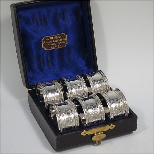 An Antique Victorian Sterling Silver set of six napkin rings, having round bodies with straight sides, hand-engraved floral decoration and  vacant rectangular cartouches, with applied bead borders, all in their original dark blue satin and velvet-lined presentation box. Made by Hilliard and Thomason of Chester in 1897. The dimensions of these fine hand-made antique silver napkin rings are diameter 4.5 cms (1.75 inches), height 2.5 cms (1 inch), and they weigh a total of approx. 127g (4 troy ounces).