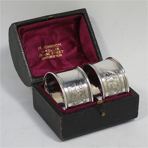 A very pretty Antique Victorian Sterling Silver pair of napkin rings, having round straight-sided bodies with applied borders, each one hand-engraved with a band of floral and scroll-work decoration, with shield-shaped vacant cartouches, and all in their original maroon satin and velvet-lined presentation box. Made by the Deakin Brothers of Chester in 1896. The dimensions of these fine hand-made antique silver napkin rings are diameter 4.5 cms (1.75 inches), height 2.5 cms (1 inch), and they weigh a total of approx. 36g (1.2 troy ounces).