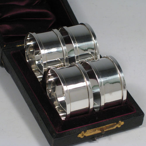 Sterling silver napkin rings in a set of four, having a very plain style, and in original maroon satin & velvet lined presentation box. All these silver napkin rings were made by Henry Griffith & Sons of Birmingham in 1931. Diameter 4.5 cms (1.75 inches), width 2.3 cms (1.85 inches). Total weight approx. 2.5 troy ounces (78g).