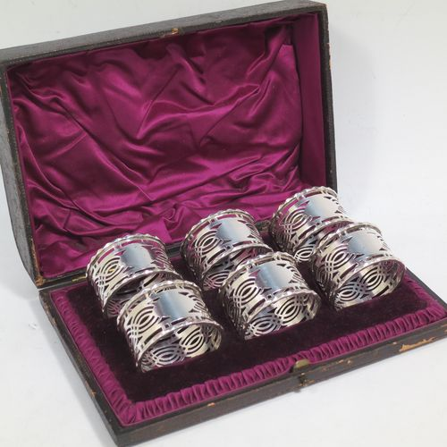 A pretty Antique Sterling Silver set of six napkin rings, having round straight-sided bodies, with hand-pierced geometrical style decoration, a central oval vacant cartouche, and with applied faceted borders, all in their original maroon satin and velvet-lined presentation box. Made by Ferganbaum and Son of Birmingham in 1921. The dimensions of these fine hand-made silver napkin rings are diameter 4.5 cms (1.75 inches), height 2.5 cms (1 inch), and they weigh a total of approx. 140g (4.5 troy ounces).