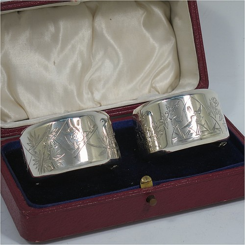 A very pretty Antique Victorian Aesthetic style Sterling Silver pair of napkin rings, having round straight-sided bodies with turned-over borders, and each one hand-engraved differently with Aesthetic decoration of birds, butterflies and bamboo shoots, all in their original cream satin and dark blue velvet-lined presentation box. Made by George Unite of Birmingham in 1881. The dimensions of these fine hand-made antique silver napkin rings are diameter 5 cms (2 inches), height 3 cms (1.25 inches), and they weigh a total of approx. 48g (1.5 troy ounces).