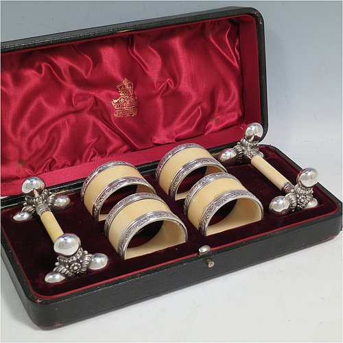 An Antique Victorian Silver-Plated and bone set of four napkin rings and two knife rests, the napkin rings having round straight-sided bodies with applied bands of floral decoration, the knife rests having cast floral supports with button ends, all in their original maroon satin and velvet-lined presentation box. Made by Elkington & Co., in ca. 1880. The dimensions of these fine hand-made antique silver plated and bone napkin rings are diameter 4.5 cms (1.75 inches), height 3 cms (1.25 inch), and the knife rests are 8.5 cms (3.3 inches) long by 4 cms (1.5 inches) high.