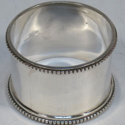 An elegant pair of Antique Edwardian Sterling Silver napkin rings, having plain round straight-sided bodies, and bead-edged borders. Made by Walker and Hall of Sheffield in 1904. The dimensions of these fine hand-made antique silver napkin rings are diameter 5 cms (2 inches), height 3 cms (1.25 inches), and they weigh a total of approx. 66g (2 troy ounces).