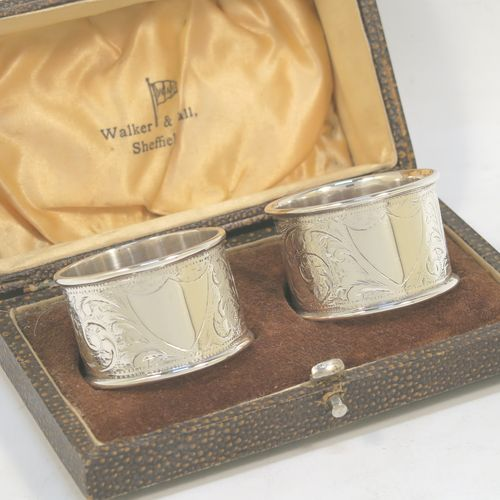 A very pretty Antique Victorian Sterling Silver pair of napkin rings, having round straight-sided bodies with hand-engraved floral decoration, and vacant shield-style cartouches, all in their original cream satin and coffee coloured velvet-lined presentation box. Made by Arthur Fenwick of Birmingham in 1900. The dimensions of these fine hand-made antique silver napkin rings are diameter 4.5 cms (1.75 inches), height 3 cms (1.25 inches), and they weigh a total of approx. 64g (2 troy ounces).