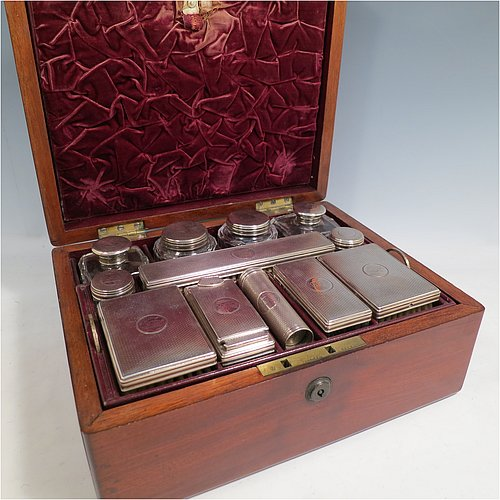 An Antique Victorian Sterling Silver travelling Necessaire, having two cologne bottles, two large bottles, two small bottles, a hair brush, two clothes brushes, an inkwell, a shaving brush, a soap box, a folding desk mirror, and internal space for letters, pens, and jewellery, all fitted in an original maroon velvet-lined oak box with brass fittings. All silver items have engine-turned decoration with central cartouches that are crested, and are made by Thomas Johnson of London in 1862. The dimensions of the solid oak box are 30.5 cms (12 inches), height 14 cms (5.5 inches), and width 24 cms (9.5 inches). Please note that the box is slightly damaged, but otherwise in excellent condition. All silver and crystal items are original with full matching hallmarks.