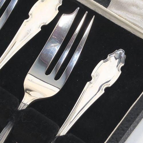 A very handsome Sterling Silver set of six pastry forks, having Chippendale or Dubarry pattern handles, and three tined forks, all in their original cream satin and black velvet-lined presentation box. Made by the Cooper Brothers of Sheffield in 1935. The dimensions of these fine hand-made silver pastry forks are length 13 cms (5.25 inches), and they weigh a total of 132g (4.3 troy ounces). Please note that the box is in good overall condition, and the lid closes properly, but the whole box is slightly warped.